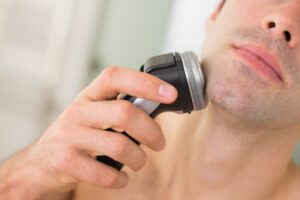 Man shaving chin with rotary shaver- Beginners Guide to Buying Electric Razor or Shaver